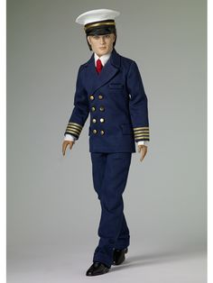 """Captain Paul  •Dressed doll  •Face includes hand-painted details  •Fine quality vinyl and hard plastic  •New Matt head sculpt  •17"""" Matt body  •Tyler skin tone  •Painted blue eyes  •Rooted brown saran hair  •Navy blue jacket with gold buttons and gold braid trim on the sleeves  •Navy blue pants  •White shirt  •Red tie  •White hat with black patent leather brim and gold braid trim  •Black molded plastic shoes  •White socks  •Stand  •LE 150"""