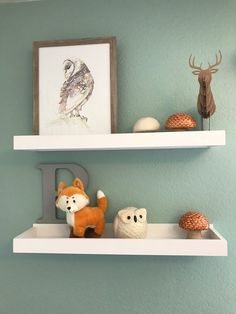 Adorable shelf styling for a woodland nursery. We love the pops of orange on the soft green walls.