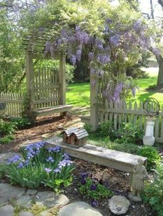 A gorgeous space to go relax with beautiful blooms. The lilacs hanging over the archway are stunning!