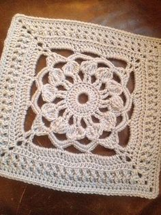 Free granny square pattern with open lace flower in the center.  Could make a nice design for a table runner or afghan.