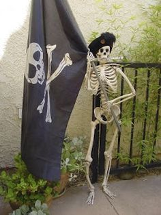 Pirate skeleton holding a pirate flag for the entry to the pirate party