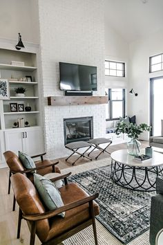 Gorgeous modern farmhouse living room designed by Sita Montgomery Interiors - white brick fireplace, simple wood mantel, leather slingback chairs, layered rugs, circular coffee table, and sconce lighting above open shelving