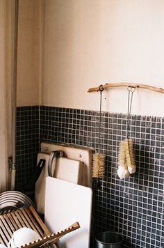 DIY simple hanging arched wood piece with hooks for dish washing accessories.