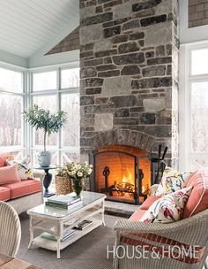 In this screened porch, a stone fireplace extends the season into late fall and early spring. | Photographer: André Rider | Designer: Scott Yetman
