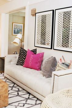Living room design with neutral sofa and black, white, and pink pops