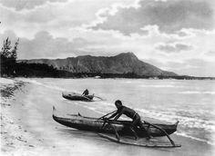 Two native Hawiians with outrigger canoes at shoreline Waikiki, Honolulu, Hawaii. c 1922