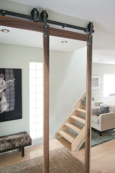 When you open the front door, you are greeted with these walnut framed mirror sliding doors on the bypass system. Just look how beautifully the walnut blends with everything in the place. That is the beauty of walnut.