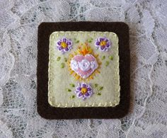 This hand-embroidered scapular (the exact one pictured above) bears the images of the Sacred Heart of Jesus and the Immaculate Heart of Mary, with columbine flowers of gold, white, light purple, and a darker purple. Columbine is a traditional floral symbol for the Holy Spirit. PRODUCT DETAILS 100% hand-embroidered, hand-made Brown Scapular Every stitch is unique (even when the design is repeated) Hearts and Cream background: 100% Merino Wool Felt Dark brown backing: 100% Woven Wool…