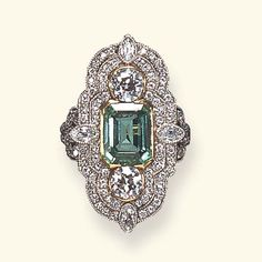 A BELLE EPOQUE EMERALD AND DIAMOND RING Set with a rectangular-cut emerald, flanked on each side by old European or marquise-cut diamonds, within an old European-cut diamond two-tiered surround, to the openwork gallery and old European-cut diamond shoulders, mounted in platinum and gold, circa 1900