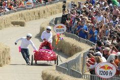 """Rose Room """"Drag"""" Racers team members Jacob Hensley and Torey Matthies push their high-heeled, shoe-shaped car toward the finish line after experiencing a wardrobe malfunction at the Red Bull Soap Box Race on Saturday, September 15, 2012. - Photo by Alexandra Olivia"""