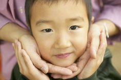 A young Asian boy's face is held tenderly in someone's cupped hands.
