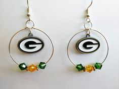 Join the huddle with these Packers hoop earrings. Green and gold Swarovski crystals are featured along with official NFL charm. Total length about