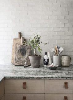 Köket är ritat av Jordens arkitekter. Färgen på kaklet och den specialbeställda bänkskivan har inspirerats av husets rikliga inslag av kolmårdsmarmor. Vintage skärbrädor, Garbo Interiors. Keramik salladsbestick från Serax, Asplund. Spräcklig sked, Merci i Paris.