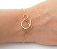 "Ampersand Bracelet. Short-hand for ""Bag & String Wine Merchants"". Wow, we should sell these in the store. Simple, not gaudy at all, and the symbol could be branded with the store. I'm a GENIUS!"