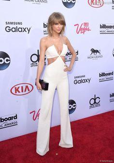 Taylor Swift apostou em um macacão branco com recortes para o Billboard Music Awards 2015, em 17 de maio de 2015. Cantora foi a grande vencedora da noite, com oito troféus