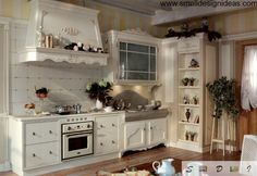 Classic Provence design for kitchen with a lot of pottery and carved exhaust hood rim