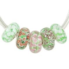 $19.49 There are five unique handmade glass beads in this beautiful set of flower garden Murano style beads. The set includes beads with pink, purple, blue, and white flowers on a green background. Each bead has a solid sterling silver core. These beads are compatible with Biaig, Ohm Beads and other major brand 3mm Cable European Charm Bracelets. Each bead measures approximately 13.5 mm x 7.5 mm.