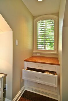 Built-in drawers create usable space in attic window wells while also conveniently housing heating & cooling vents.