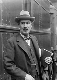 "Howard Carter standing with a book in his hand next to a train at a station in Chicago, 1925, Illinois. Howard Carter (1874-1939) was an English archaeologist and Egyptologist who became world famous after discovering the intact tomb of 14th-century BC pharaoh Tutankhamun (colloquially known as ""King Tut"" and ""the boy king"") in November 1922."