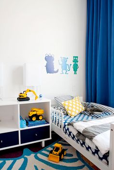 Little boy's bedroom with yellow and blue patterned bedding and cute art above bed