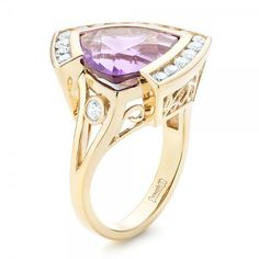 Custom Amethyst and Diamond Fashion Ring #102958-This stunning ladies' fashion ring features a trillion cut amethyst bezel set in yellow gold, surrounded by a halo of channel set diamonds, and accented with custom filigree on the split shank. It was created for a client from Seattle, WA . $7,042
