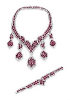 FROM THE COLLECTION OF ELIZABETH TAYLOR - A SUITE OF DIAMOND AND RUBY JEWELRY Comprising a necklace, the front suspending five cushion-cut ruby cluster pendants, each within a circular-cut diamond surround, to the V-shaped neckchain of similar design; and a bracelet en suite, mounted in 18k white gold.