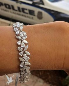 Diamonds set up like a bangle of flowers are perfect for a sweet lady. What a…
