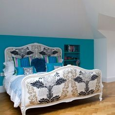 Gorgeous bed with fabric covered head and foot boards against turquoise accent wall