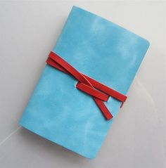 Leather Notebook / journal / travel booklet / sketch book pocket size in blue turquoise leather and a red leather strap. €10.95, via Etsy.