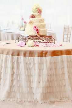 Ruffled burlap table skirt...good idea for the cake table or maybe under a dessert or beverage station. The layers of tulle cascading down the sides give it an elegant touch. (scroll down to #23 on the page). #MyOnlineWeddingHelp