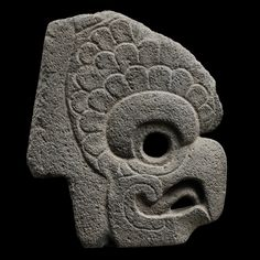 View 1: Ceremonial Hacha Representing a Macaw - Veracruz - The sharp hooked beak is half-open and shows the openwork-designed tongue. The round eye is pierced and is surrounded by a circular line. The lower eyelid, marked by an incision, is sculpted with a slight relief. The upper eyelid, thick and in relief, is encircled by a triple row of elements into a fan shape, evoking the feathers. The flattened forehead represents the sharp part of the hacha.