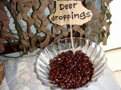 """Hunting themed birthday party.  These made laugh out loud when I decided to do them! These are coffee bean candies I found in an online candy store.  They really do look like """"deer droppings!""""  Sign was made by running a paper bag through my home inkjet printer, torn out and then glued to a washed off stick.  :)"""