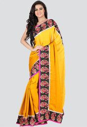 Embrace your femininity with this embroidered chiffon saree. The patch patti border illustrates unique style and the amber yellow shade traces elegance with apt contrast. Wear it with pink, scoop neck blouse and pink sandals for a delighted look.