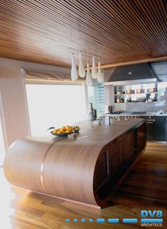 Walnut curved kitchen island unit with copper inlays. Slatted timber ceiling with recessed lighting and Iatanza flooring