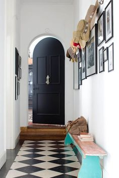 A narrow entry with style,black front door  checkered floor