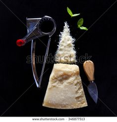 a piece of Parmesan cheese on dark with a manual cheese grater and a knife for chopping hard cheese