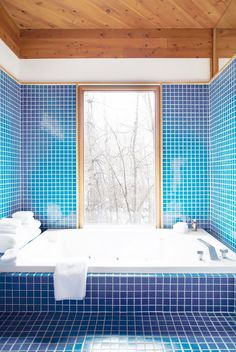 '70s inspired bathroom with royal blue mosaic tiles and wood ceilings