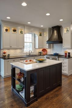Kitchen full of contrasts: white cabinetry with black countertops are paired with a black wood island with white countertop, over natural hardwood flooring.