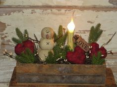 I have made this arrangement in a primitive lath box container. I  have added three of my hearts, snowman, pine, berries with a grungy  tag that says  Love with a key. I have added a electric light to the arrangement.  Measures approx 9 x 13 high.  Due to the nature of being handmade, slight variations may occur in placement of items.  Nice accent for your primitive winter decor.