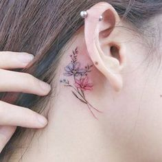 Flower tattoos behind the right ear.
