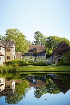 In the garden, buildings are reflected in the still lake. Family home in restored and modernised barn in Suffolk – pale and rustic country interiors.