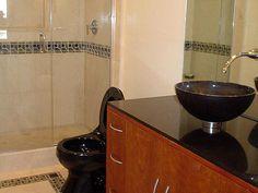 neutral walls, floor...black counter, toilet and wood vanity