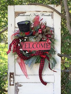 This Cozy and Happy Christmas Wreath is made on a Pine Base. I have Layered it with an Assortment of Pine, Frosted and Icy Pine and Red and White Berries. I Added a Wooden Rustic Look Welcome Sign and the Cutest Sparkly Snowman Hat. I Finished out the Wreath with an Assortment of Wired Black Homespun Ribbon, Wired Snowflake Print Ribbon, Red Deco Mesh and a Black and Red Checked Wired Ribbon. This Wreath Measures 33 in Length and is 27 Across. This is Measuring Tip to Tip but DOES NOT…