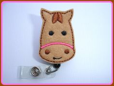 Adorable horse head in tan felt machine embroidered with brown, black and pink thread throughout. Applique measures 1 3/8 x 2. Applique