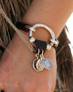 Interesting way of fastening charms, through a folded piece of leather. Source unknown.