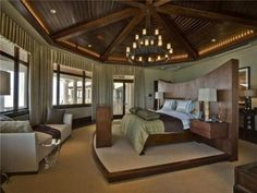 Master Bedroom; wood plank & beam ceiling, bed on pedestal, window surround