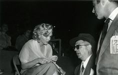 MARILYN MONROE chatting with entertainer, KEN MURRAY, at a Rams vs. Redskins football game taken August 21, 1952. Ms. Monroe and Mr. Murray provided some entertainment at halftime together with SPIKE JONES.
