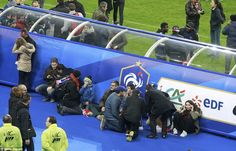 Spectators wait on the pitch of the during the match between France and Germany at Stade de France after two suicide bombers detonated explosives outside