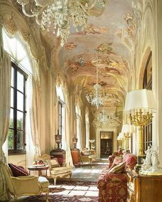 This Renaissance palazzo in Florence has several window spaces and seating areas. Each window space is defined by a decorative rug. The red rug in the foreground resonates with the red sofa. The seating area in the far distance has a gold decorative rug that picks up the beige and golds of the upholstered chairs.