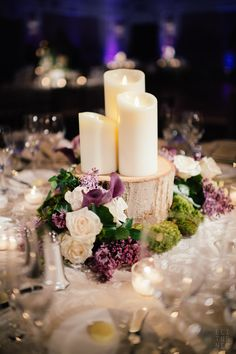 Centerpieces consisted of candles on wood slabs arranged with ivory and purple roses, purple calla lilies and moss.